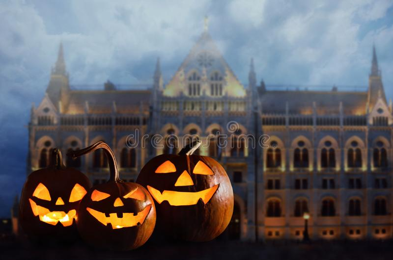 Halloween pumpkin head jack lanterns in front of ancient spooky castle royalty free stock images