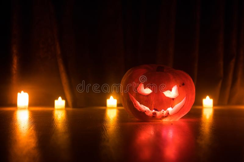 Halloween pumpkin head jack o lantern with glowing candles on background. Pumpkins on wooden floor. Selective focus royalty free illustration