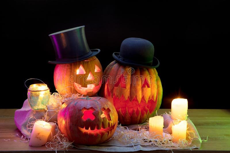 Halloween pumpkin head jack lantern with scary evil faces and candles. Halloween pumpkin head jack-o-lantern in hats with scary evil faces and candles. Seasonal stock image