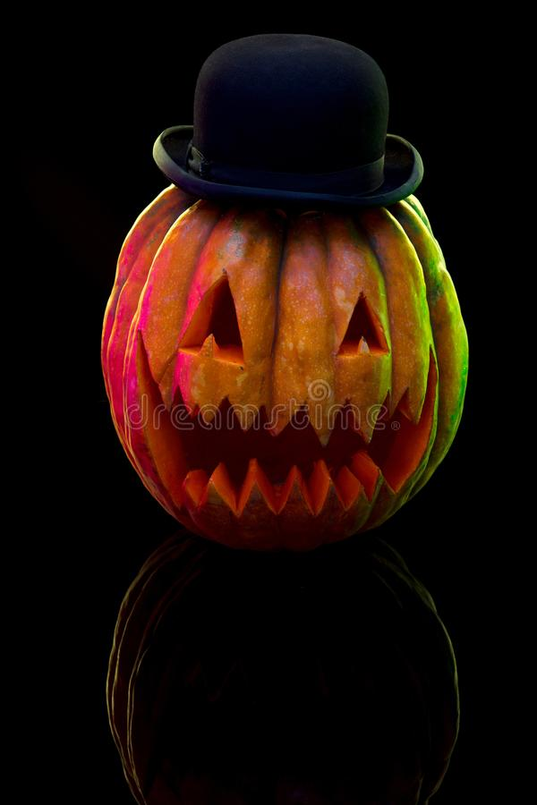 Halloween pumpkin head jack lantern with scary evil face. Halloween pumpkin head jack-o-lantern with scary evil face and hat. Seasonal illuminated decoration royalty free stock images