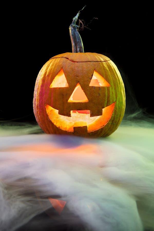 Halloween pumpkin head jack lantern with scary evil face. Halloween pumpkin head jack-o-lantern with scary evil face. Seasonal illuminated decoration. Looks stock photos