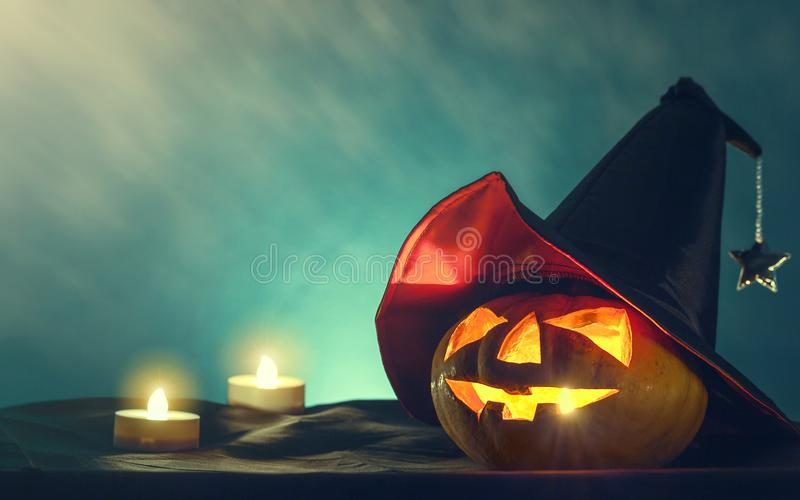 Halloween pumpkin head with witch hat and candle light in darkness spooky background. Halloween background stock photo