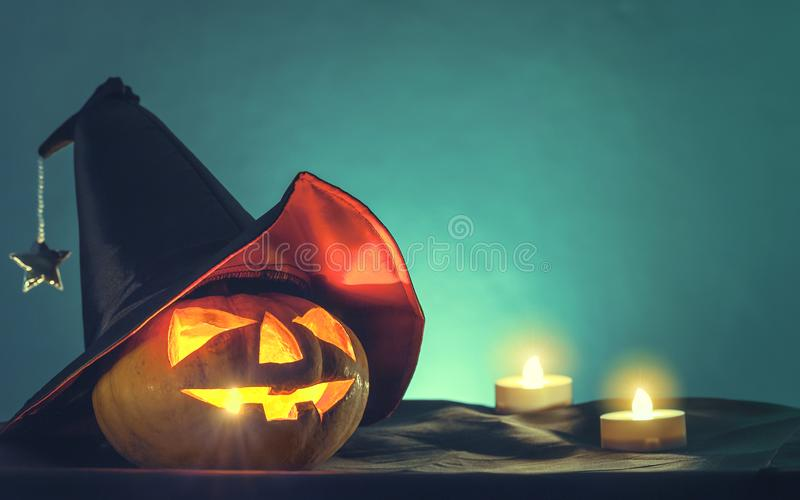 Halloween pumpkin head with witch hat and candle light in darkness spooky background. Halloween background stock image