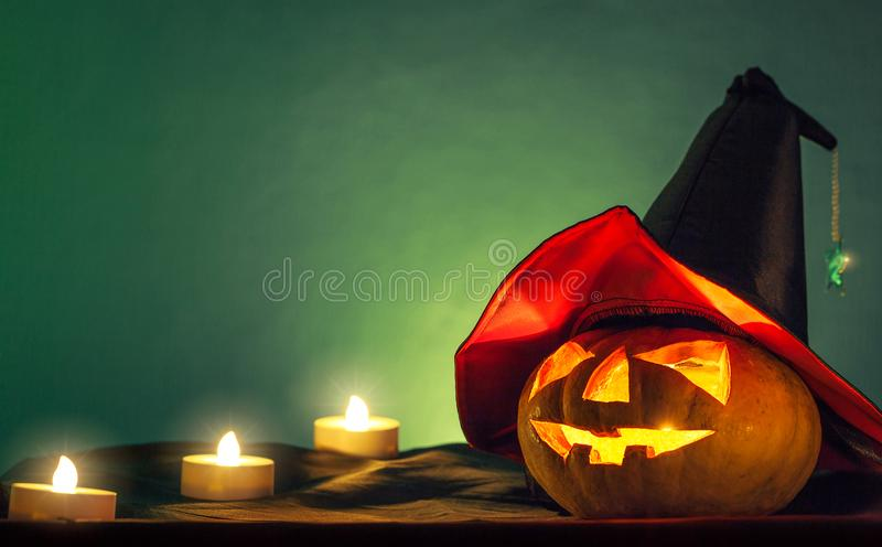 Halloween pumpkin head with witch hat and candle light in darkness spooky background. Halloween background royalty free stock photography