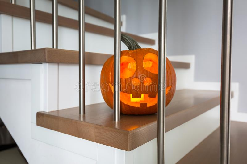 Halloween pumpkin on the house stairs glowing in the dark stock images