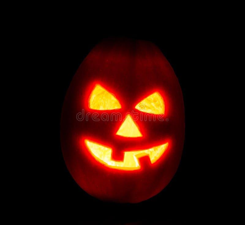 Halloween pumpkin jack-o-lantern candle lit, isolated on black stock photo