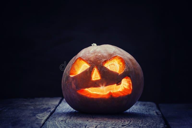 Halloween pumpkin Jack-o-Lantern on the dark wood background, se royalty free stock photos