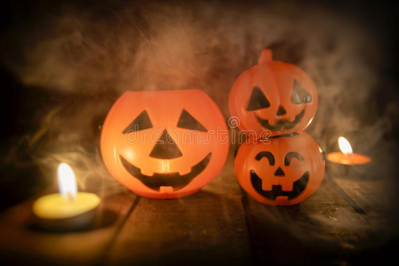 Halloween pumpkin lantern candle light on wooden with smoke - head jack o lantern funny faces spooky holiday decorate on halloween. Halloween pumpkin lantern royalty free stock images