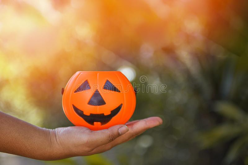 Halloween pumpkin lantern on hand - head jack o lantern evil faces spooky holiday decorate on halloween nature background. Halloween pumpkin lantern on hand / stock photography