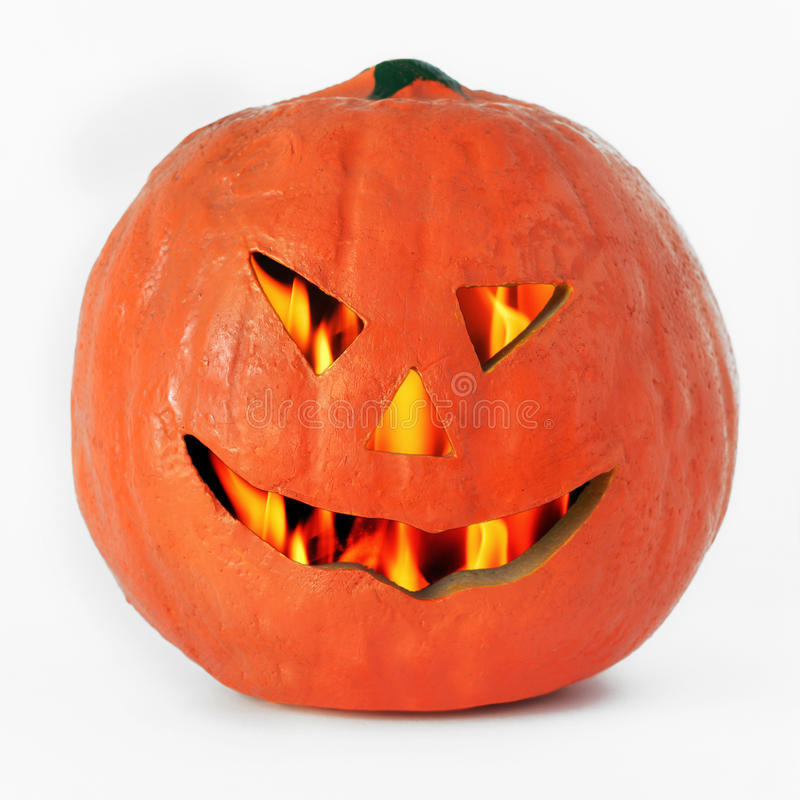 Halloween pumpkin lantern. Or jack-o-lantern, with a scary cut out face and a flaming interior , closeup on a white background stock images