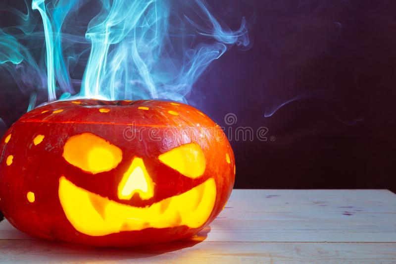 Halloween pumpkin monster with many round holes emitting smoke stock photography