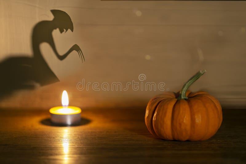 Halloween pumpkin on old wooden background. Spirit monster behind. Shadow theatre concept stock image