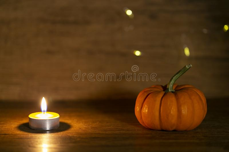 Halloween pumpkin on old wooden background. Warm lights behind stock photography