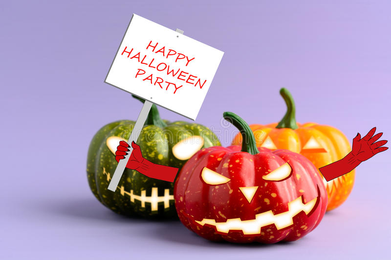 Halloween pumpkin with a poster in his hand. On a purple background stock photo