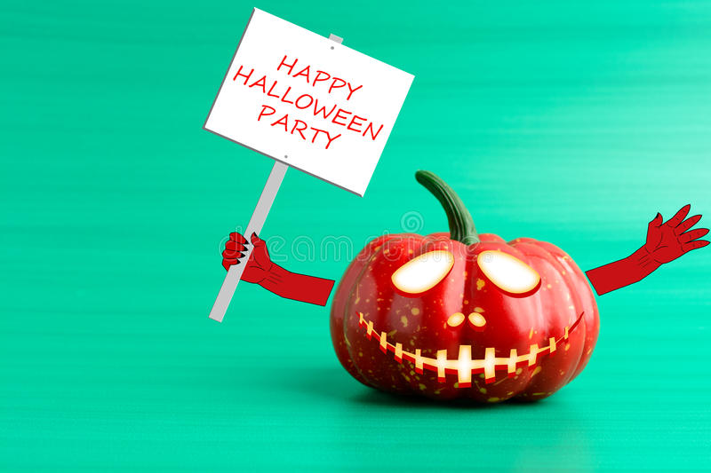 Halloween pumpkin with a poster in his hand. On a turquoise background royalty free stock images