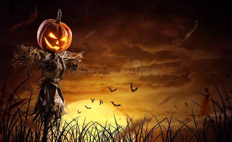 Halloween pumpkin scarecrow on a wide field with the moon on a scary night.  stock images