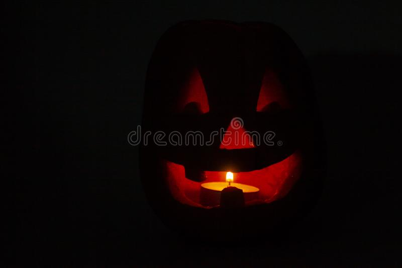 Halloween pumpkin with scary face and burning candles stock photography