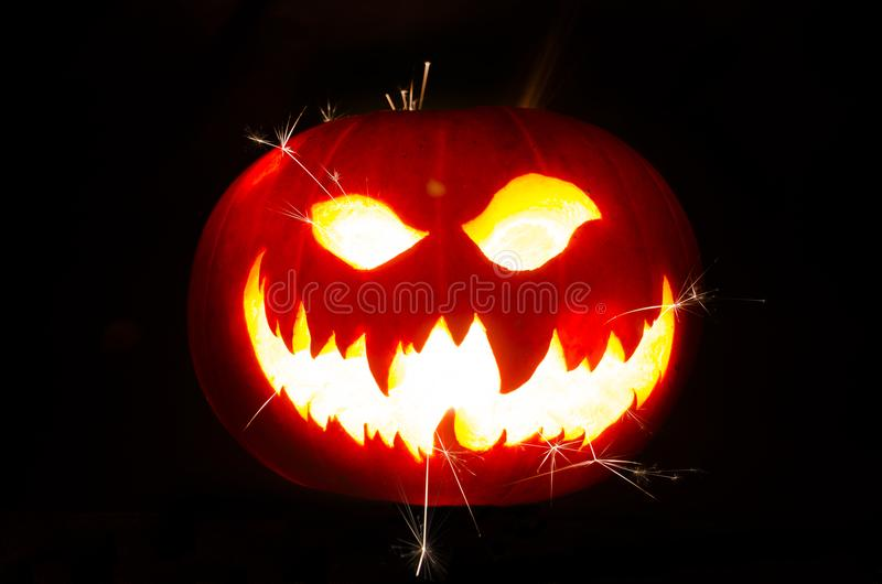 Halloween Pumpkin with Scary Face and Sparks. Isolated Halloween Pumpkins with the writing a scary Face with sparks coming out royalty free stock images