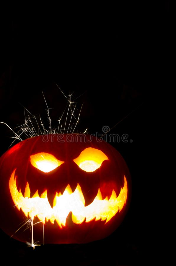 Halloween Pumpkin with Scary Face and Sparks. Isolated Halloween Pumpkins with the writing a scary Face with sparks coming out royalty free stock image