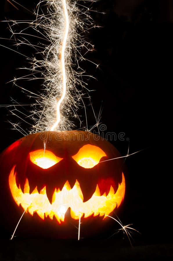 Halloween Pumpkin with Scary Face and Sparks. Isolated Halloween Pumpkins with the writing a scary Face with sparks coming out stock photos