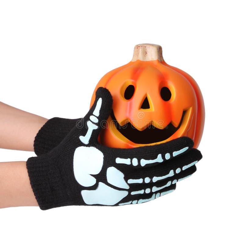 Halloween pumpkin in skeleton hands. Halloween pumpkin in hands with skeleton print gloves isolated on white stock photography