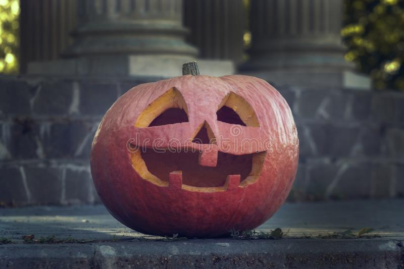Halloween pumpkin with a smiling face. Brightly orange vegetable at dusk. stock photography