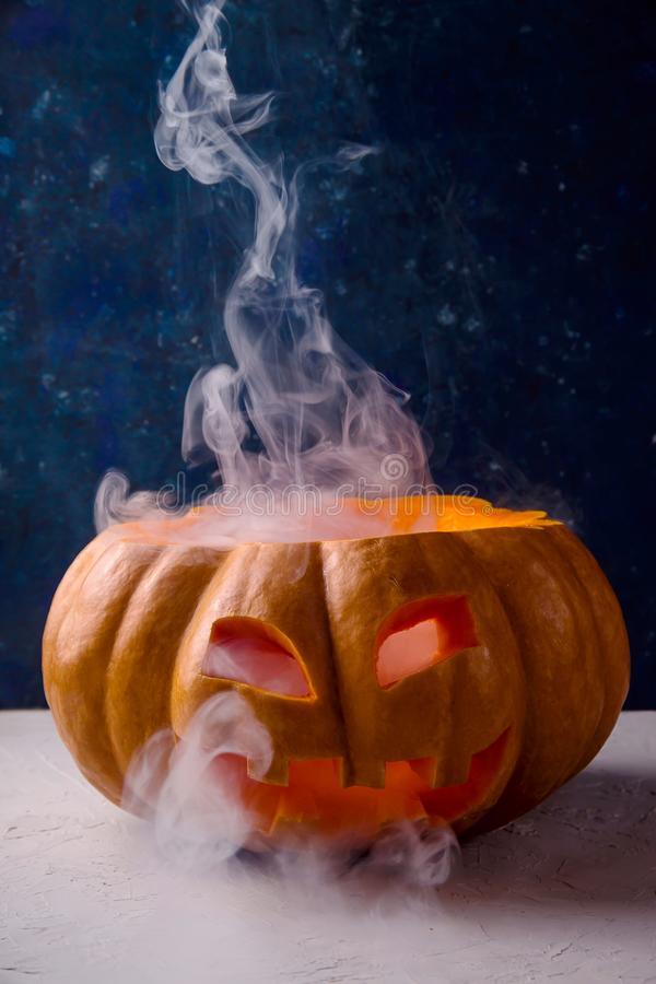 Halloween pumpkin with smoke from eyes and mouth. A large pumpkin with a carved face as a symbol of Halloween with white smoke from it on a blue background stock photo