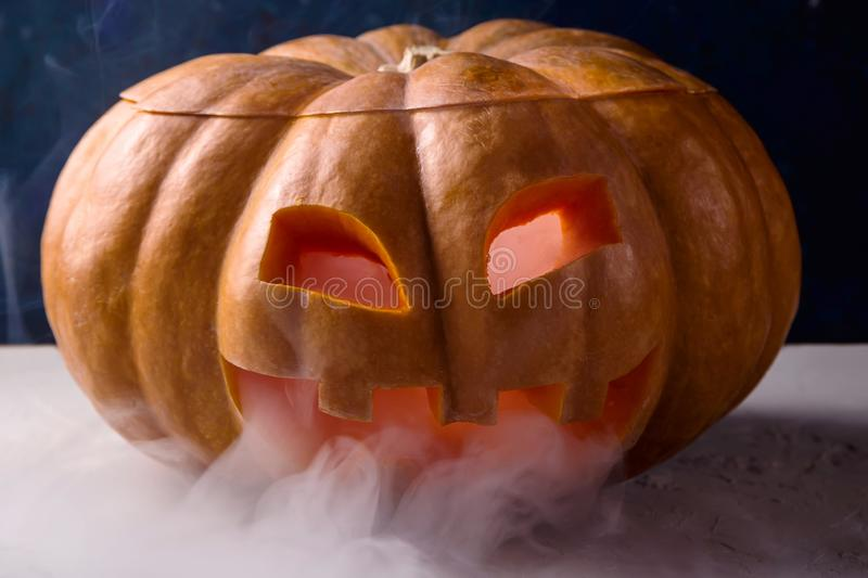 Halloween pumpkin with smoke from eyes and mouth. A large pumpkin with a carved face as a symbol of Halloween with white smoke from it on a blue background royalty free stock photography