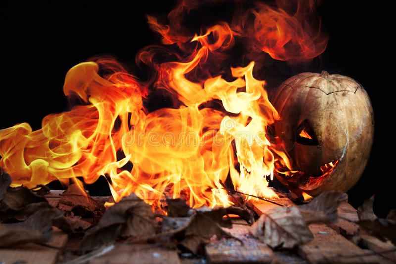 Halloween pumpkin spewing flames of fire on a black background. Fear stock image