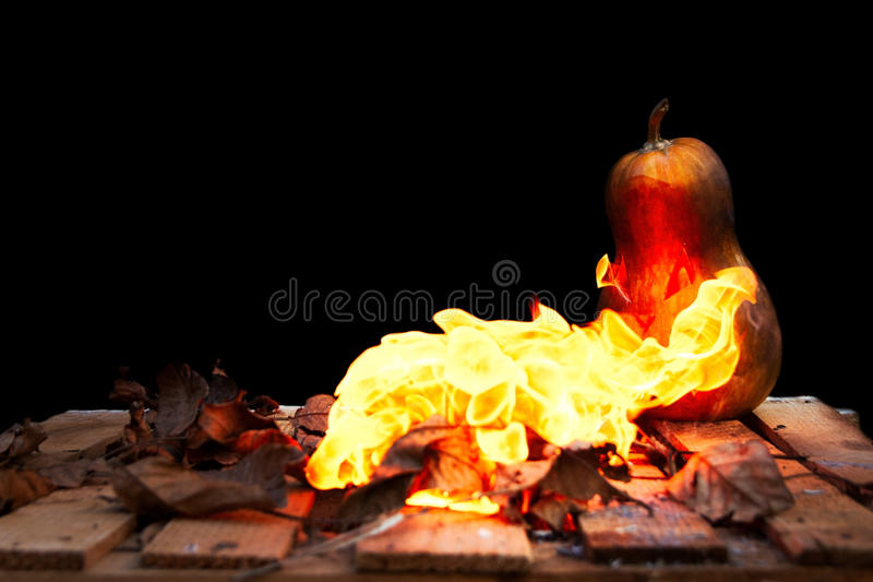 Halloween pumpkin spewing flames of fire on a black background. Halloween pumpkin fear and spooky spewing flames of fire on a black background royalty free stock images
