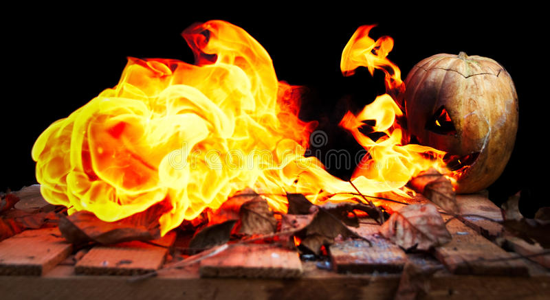 Halloween pumpkin spewing flames of fire on a black background. Fear and spooky stock photos