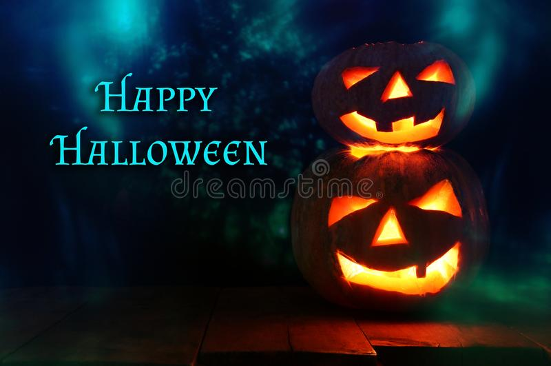 Halloween Pumpkin on wooden table in front of spooky dark background. Jack o lantern.  stock photo
