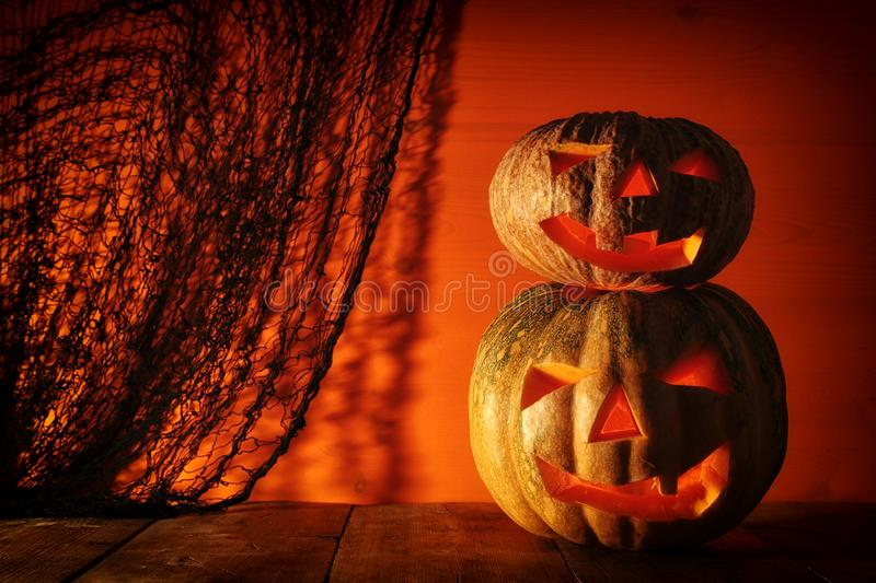 Halloween Pumpkin on wooden table in front of spooky dark background. Jack o lantern.  royalty free stock images