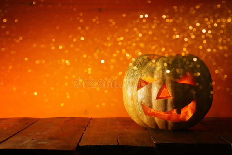 Halloween Pumpkin on wooden table in front of spooky dark background. Jack o lantern.  stock images