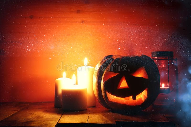 Halloween Pumpkin on wooden table in front of spooky dark background. Jack o lantern.  royalty free stock photo
