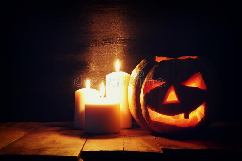 Halloween Pumpkin on wooden table in front of spooky dark background. Jack o lantern.  stock photos