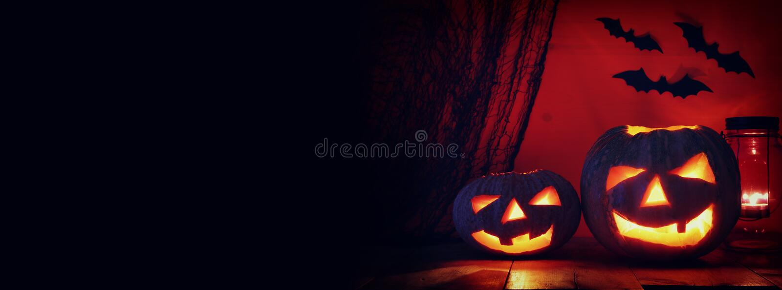 Halloween Pumpkin on wooden table in front of spooky dark background. Jack o lantern.  stock image