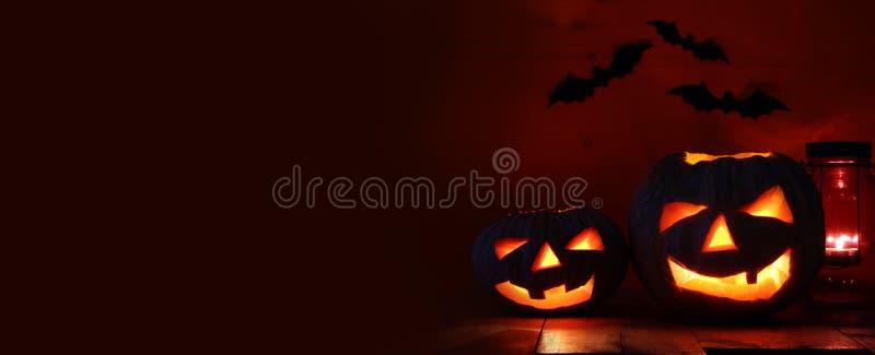 Halloween Pumpkin on wooden table in front of spooky dark background. Jack o lantern stock photo
