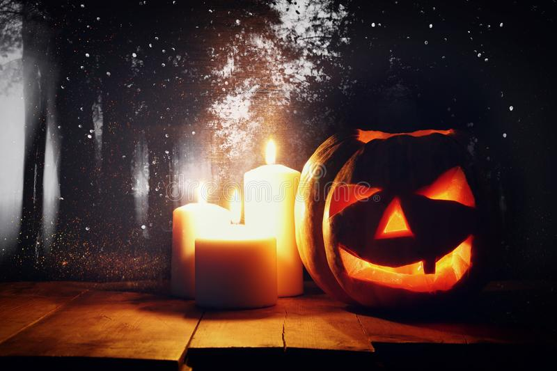 Halloween Pumpkin on wooden table in front of spooky dark background. Jack o lantern.  royalty free stock photos