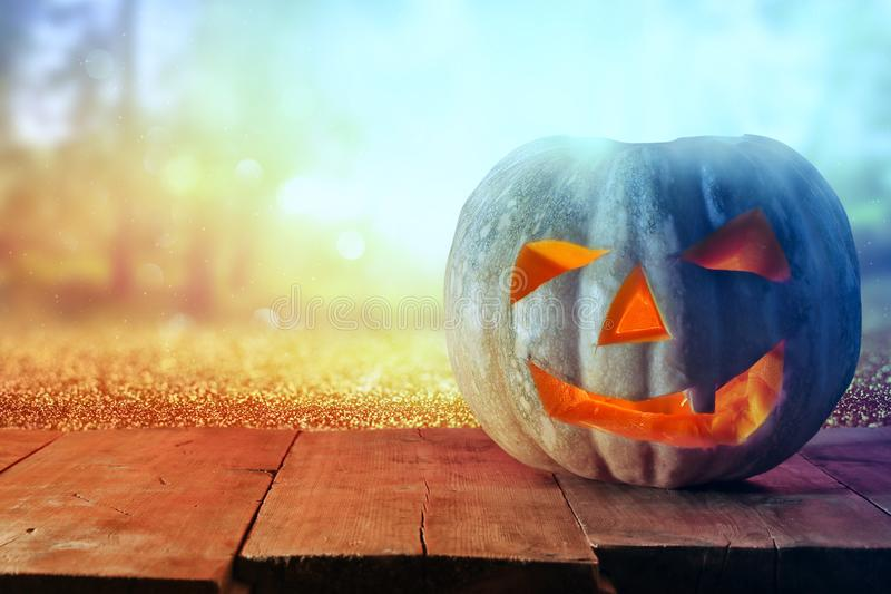 Halloween Pumpkin on wooden table in front of spooky dark background. Jack o lantern.  royalty free stock photography