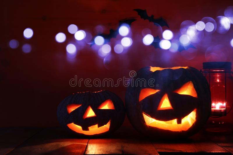 Halloween Pumpkin on wooden table in front of spooky dark background. Jack o lantern.  stock photography