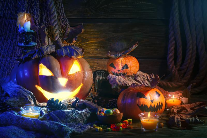 Halloween pumpkins and candy on wooden table at night. stock image