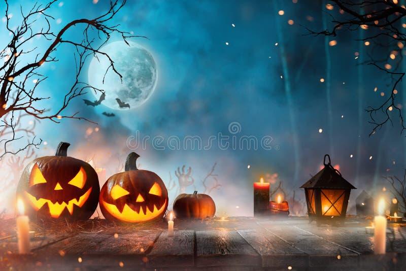 Halloween pumpkins on dark spooky forest. Halloween pumpkins on dark spooky forest with blue fog in background stock image