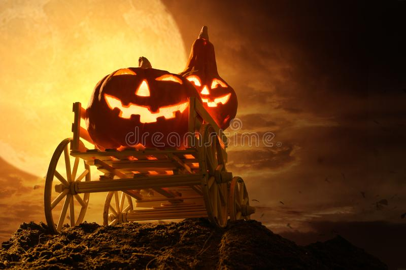 Halloween pumpkins on farm wagon at spooky in night of full moon stock images