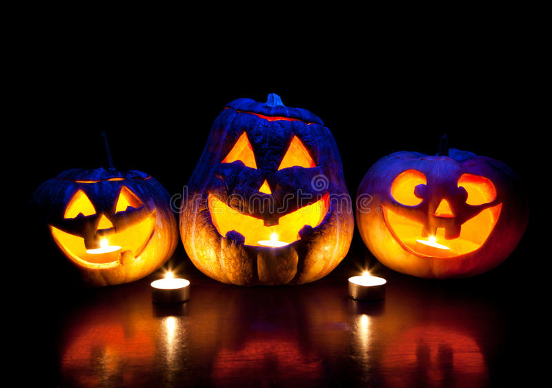 Halloween pumpkins glowing inside. Scary Halloween pumpkins with eyes glowing inside at black background royalty free stock photography