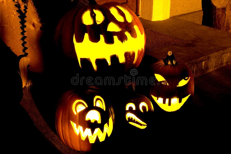 Halloween pumpkins at night in front of the door. Several illuminated Halloween pumpkins at the entrance of a house royalty free stock images