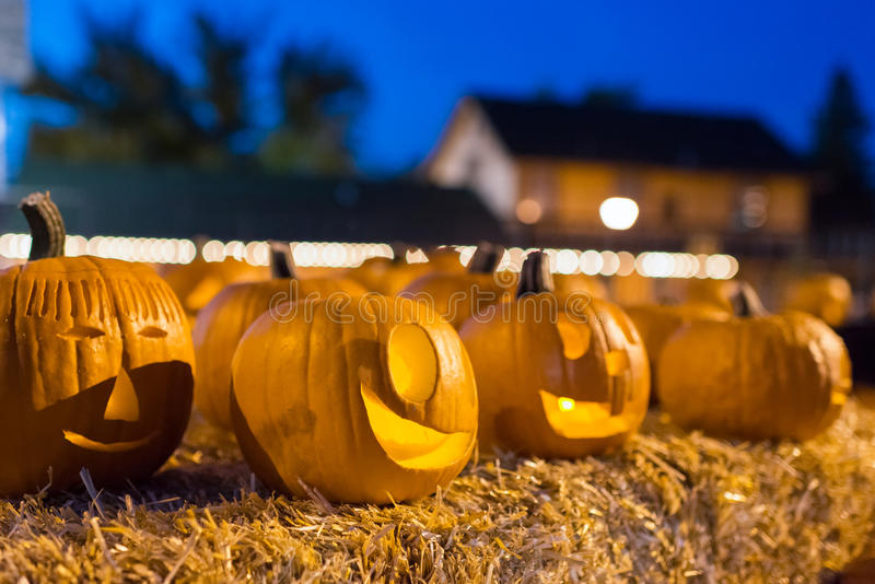 Halloween pumpkins at night on hay bale. Group of carved halloween pumpkins lit with candles sitting on a hay bale at dusk under a blue sky. Shot with a shallow stock images