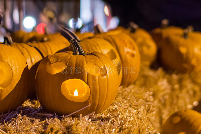 Halloween pumpkins at night on hay bale. Group of carved halloween pumpkins lit with candles sitting on a hay bale at night. Shot with a shallow depth of field royalty free stock photos