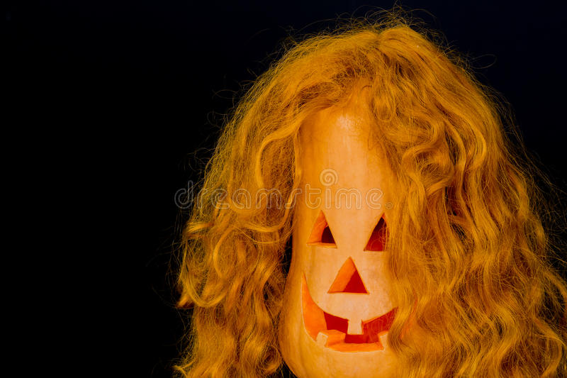 Halloween pumpkins , scary face , background. Halloween pumpkins with very scary face and with red hair, burning candle on black background. With your place for royalty free stock photos