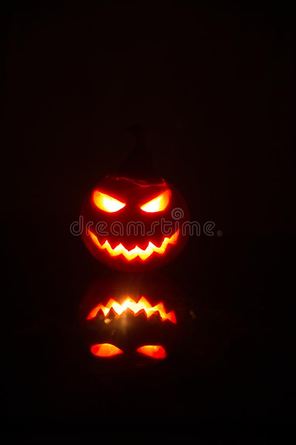 Halloween pumpkins smile and scrary eyes for party night. Close up view of scary Halloween pumpkin with eyes glowing inside at bla stock image